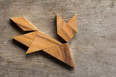 Drewniany tangram jako działający kota kształt na drewnianym tle Fotografia Stock