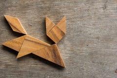Drewniany tangram jako działający kota kształt na starym drewnianym tle Obrazy Stock