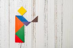 Drewniany tangram kształtował jak ludzi trzyma coś Obrazy Royalty Free