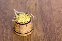 Drewniany wiadro z jagłą na drewnianym stole Smakowita i pożytecznie zboże owsianka z go Obrazy Royalty Free