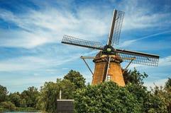 Drewniany wiatraczek, obfitolistni krzaki i pogodny niebieskie niebo przy Weesp, Zdjęcia Stock