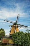 Drewniany wiatraczek, obfitolistni krzaki i pogodny niebieskie niebo przy Weesp, Fotografia Stock