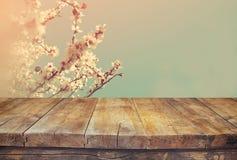 Drewniany wieśniaka stół przed wiosen białymi czereśniowymi okwitnięciami drzewnymi rocznik filtrujący wizerunek produktu pokaz i Fotografia Stock