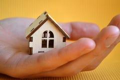 Drewniany zabawka domu model w mężczyzna ręce na żółtego tła frontowym widoku obraz stock