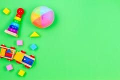 Drewniany zabawka pociąg, dziecka sztaplowanie dzwoni ostrosłupa, balowych i kolorowych bloki na zielonym tle, fotografia royalty free