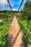 Drewniany zawieszenie most nad rzeką w Karpackiej górze obrazy stock