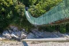 Drewniany zawieszenie most przez szeroką halną rzekę obraz royalty free