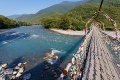 Drewniany zawieszenie most przez szeroką halną rzekę na słonecznym dniu obraz stock
