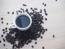 Drewno stół z czarną filiżanką i kawową fasolą Obrazy Stock
