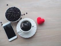 Drewno stół z gorącą czarną kawą, kawowa fasola, czerwony kierowy kształt s Fotografia Royalty Free