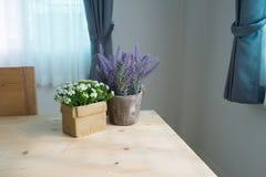 Drewno stół z grupą piękny sztuczny kwiat na garnku przy l Zdjęcia Stock