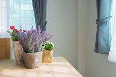 Drewno stół z grupą piękny sztuczny kwiat na garnku przy l Obrazy Stock
