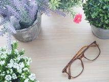 Drewno stół z piękną kwiat ramą na garnku i nowożytnych eyeglas Zdjęcia Royalty Free