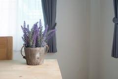 Drewno stół z sztucznym purpurowym lawendowym kwiatem na garnku przy livi Obrazy Royalty Free