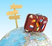 Drewno znaka deskowa i stara walizka z striples zaznacza na zamazanej światowej mapie Fotografia Stock