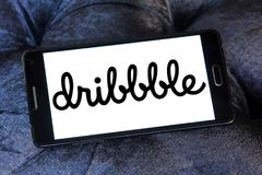 Dribbble online community logo. Logo of Dribbble on samsung mobile. Dribbble is an online community for showcasing user made artwork. It functions as a self stock image