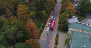Dribe rojo en el vuelo del abejón del camino de ciudad, árbol amarillo del autobús metrajes
