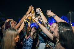 Dricka öl som tillsammans tycker om musikfestival royaltyfri bild