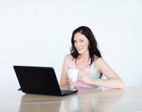 dricka bärbar dator för kaffe genom att använda kvinnan Arkivfoton