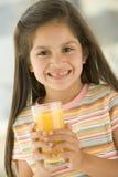 dricka barn för fruktsaft för flicka inomhus orange le Arkivfoto