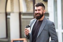 Dricka det på går Skäggig hipster för man att föredra kaffe för att ta bort Affärsmandrinkkaffe utomhus Läggande tillbaka energi royaltyfri bild