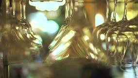 Dricka exponeringsglas för coctailen som hänger ovanför stångräknare i nattklubb Slut upp tomma exponeringsglas för vin och alkoh arkivfilmer