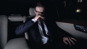Dricka exponeringsglas för miljonär av elitkonjak på baksätet av bilen, affärstur stock video