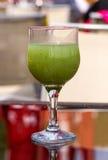 Dricka exponeringsglas med den gröna drycken Arkivbilder