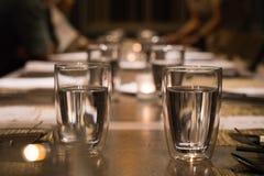 Dricka exponeringsglas på den äta middag tabellen arkivfoto