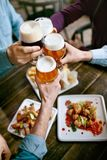 dricka för öl Vänner som lyfter exponeringsglas av öl royaltyfri fotografi