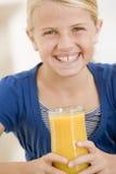 dricka för fruktsaftorange för flicka inomhus barn Arkivfoto