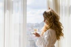 dricka flicka för skönhetkaffe Härliga kvinnaöppningsgardiner som ut ser fönstret och tycker om hennes morgonkaffe Arkivbilder