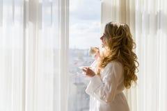 dricka flicka för skönhetkaffe Härliga kvinnaöppningsgardiner som ut ser fönstret och tycker om hennes morgonkaffe Royaltyfri Foto