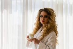 dricka flicka för skönhetkaffe Härliga kvinnaöppningsgardiner som ut ser fönstret och tycker om hennes morgonkaffe Royaltyfri Bild