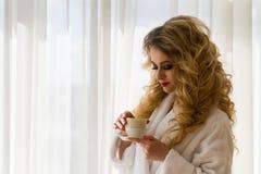 dricka flicka för skönhetkaffe Härliga kvinnaöppningsgardiner som ut ser fönstret och tycker om hennes morgonkaffe Arkivfoto