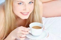 Dricka kaffe för kvinna i säng Royaltyfri Bild
