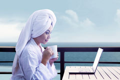 Dricka kaffe för kvinna vid bärbar dator Royaltyfria Bilder