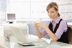 Dricka kaffe för ung affärskvinna på skrivbordet royaltyfri foto