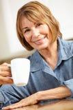 Dricka kaffe för mitt- ålderkvinna Royaltyfria Bilder