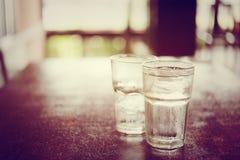 Dricka kallt vatten in i ett tre exponeringsglas som förläggas på trätablen Royaltyfri Foto