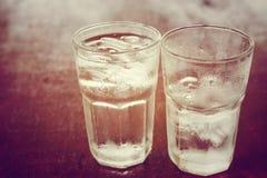 Dricka kallt vatten in i ett tre exponeringsglas som förläggas på trätablen Fotografering för Bildbyråer