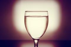 Dricka kallt vatten in i ett tre exponeringsglas som förläggas på trätablen Arkivfoton