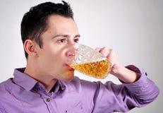 Dricka öl för ung man Arkivfoton