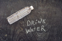 Dricka mer vatten - hydrationpåminnelse - handskrift på på ett kritabräde Arkivfoto