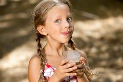 Dricka milkshake för uttrycksfull flicka. Royaltyfri Fotografi