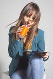 Dricka refreshment för ung affärskvinna genom att använda sugrör royaltyfri bild