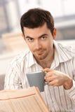 Dricka tea för ung manavläsningsnyheterna hemma royaltyfria foton