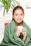 Dricka tea för kvinna hemma som räknas med filten Royaltyfri Bild