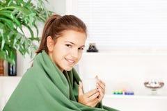 Dricka tea för kvinna hemma som räknas med filten Arkivfoton