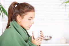 Dricka tea för kvinna hemma som räknas med filten Royaltyfria Bilder